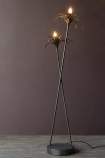 Lifestyle image of the Two Palm Reeds Floor Lamp lit up with dark wall background and dark wooden flooring