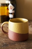 Lifestyle image of the Two-Tone Ochre & Terracotta Mug on wooden shelf with bottles on it and pale wall background