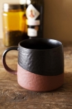 Lifestyle image of the Two-Tone Black & Terracotta Mug on wooden shelf with bottles on and pale wall background
