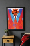 Front on lifestyle image of the Unframed A Clockwork Bowie Art in black frame hanging on grey wall Print above wooden side table with plant and chair with lightening bold print on