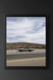 lifestyle image of Unframed Bisbee Roadside Art Print in black frame on dark grey wall background