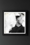 lifestyle image of Unframed Faceless No.1 Fine Art Print black and white boy with eyes, nose and mouth whited out in black frame on dark wall background