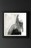lifestyle image of Unframed Faceless No 3 Fine Art Print black and white girl with face whited out in black frame on dark wall background