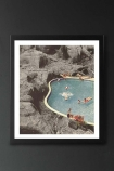 lifestyle image of Unframed Is This The Place That They Call Fine Art Print blue pool with people in and grey rocks in background in black frame on dark wall background