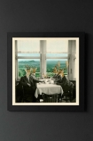 lifestyle image of Unframed The Gang Fine Art Print deer in suits around table in black frame on dark wall background