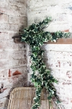 lifestyle image of Faux Variegated Ivy Plant on shelf above rattan chair with distressed white brick wall background