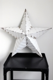 lifestyle image of Vintage Metal Star - White on grey tray side table and white wall background
