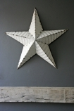 lifestyle image of Vintage Metal Star - White above grey wooden panel and on dark grey wall background