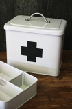 lifestyle image of Vintage Style Tin First Aid Box on wooden table with dark wall background