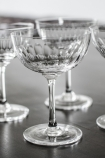 lifestyle image of Set Of 6 Vintage Style Crystal Champagne Saucers - Lens with other glasses in background on black table