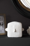 Lifestyle image of the White Concrete Stan Statue on black mantel with round mirror and picture frame in background