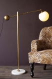 Lifestyle image of the Atlas Globe Angled Floor Lamp With Marble Base switched on with Rockett St George Leopard Love Armchair on dark wooden flooring and dark purple wall background