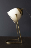 lifestyle image of White & Brass Lola Desk Lamp on black table with dark wall background