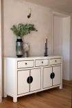 Angled lifestyle image of the Oriental Gloss White Sideboard