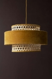 Lifestyle image of the Gold Mustard Woven Cane & Velvet Cylinder Pendant Ceiling Light on a dark brown wall background