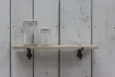 landscape lifestyle of Oak Shelf With Cast Iron Brackets - Small with two glass jars on top and white wood panel wall background