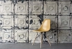 landscape lifestyle image of NLXL TIN-01 Brooklyn Tin Tiles Wallpaper By Merci with yellow chair on grey flooring