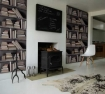 A living room featuring a log burner, cowhide rug and bookshelf wallpaper