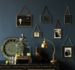 Brass and glass picture frames featured on a dark blue wall with a weathered black wardrobe in front