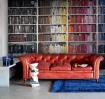 square lifestyle image of Mr Perswall Communication  Library, Colourful Knowledge - Black/Brown P131501-4 behind red leather sofa and blue rug on grey flooring