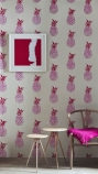 lifestyle image of Barneby Gates Pineapple Wallpaper - Pink/Red with two side tables and wooden chair with pink cushion and pink art in frame on wall