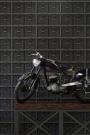 Lifestyle shot of the industrial basket wallpaper with a trestle table featuring a mini retro motorcycle on it - Rockett St George