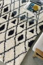 Lifestyle shot of a diamond pattern deep pile African rug under a glass table - Rockett St George
