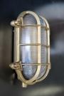 Vintage brass oval bulkhead light on a metal wall