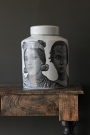White fornasetti ceramic jar with faces on it on a wooden marble effect table