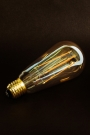 Image of the E27 3W LED Dimmable Tinted Squirrel Cage Light Bulb tilted on a black background