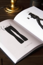 Lifestyle image of the All Black Everything book open with an illustration on a coffee table