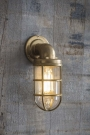 Lifestyle image of the Nautical Inspired Brass Bulkhead Down Wall Light lit up on the wall