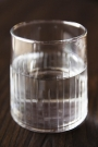 Close-up image of the Elegant Engraved Stripes Tumbler Water Glass with water in it
