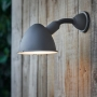 The charcoal coloured outdoor wall light attached to a wooden wall lights up a garden