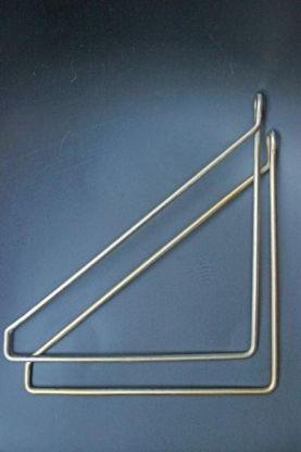 2 brass shelf hangers laying sideways on a dark blue background