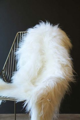 lifestyle image of Genuine Icelandic Long Wool Sheepskin - Natural White on midas chair with dark wall background