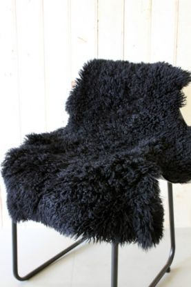 genuine sheepskin rug - curly black on black chair with white background lifestyle image