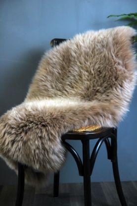 genuine sheepskin rug - silky taupe on black chair with dark blue background lifestyle image