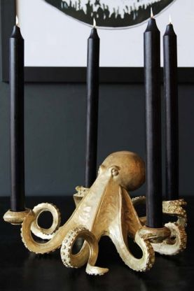 lifestyle image of gold octopus candlestick holder with black tall candles in and black on black table and white print in background