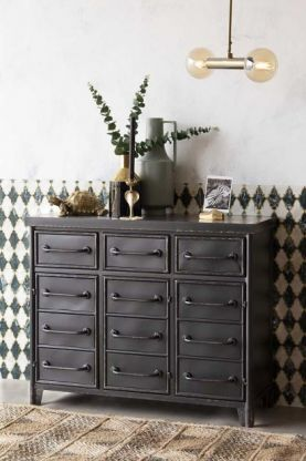 Lifestyle image of the Industrial-Style Black Metal Drawer Storage Cabinet with ceiling light and patterned wall background
