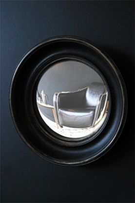 little aged black convex mirror angled on dark background lifestyle image