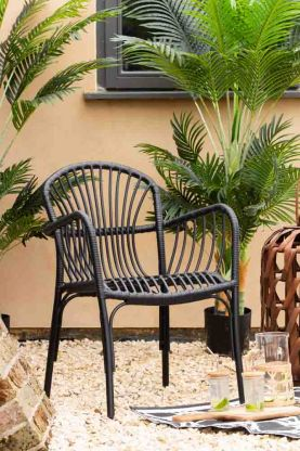 Close-up lifestyle image of the Brea Black Garden Chair in the garden