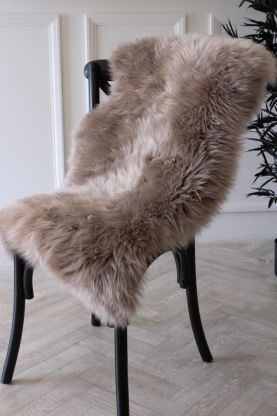 lifestyle image of genuine sheepskin rug - silky light grey on black chair on wooden flooring and white wall background