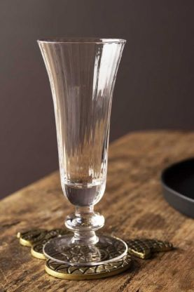 Lifestyle image of the Ribbed Glass Champagne Flute on a gold snake coaster on wooden table wit dark wall background