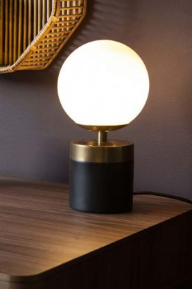 Lifestyle image of the Atlas Globe Table Lamp With Black & Brass Base switched on on wooden table and rattan shelf unit on dark wall background