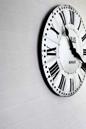 Lifestyle image of Anaglypta Lincolnshire Brick Wallpaper with large black and white clock