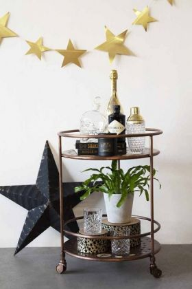 lifestyle image of Antique Copper Shoreditch Drinks Trolley full of drinks and plant in white pot with black star decoration on floor and gold star bunting on white wall background