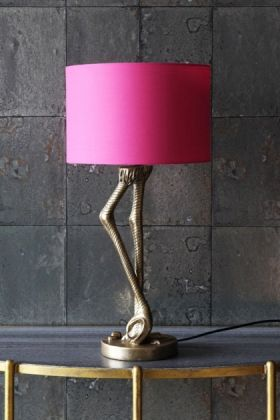 lifestyle image of antique gold flamingo leg table lamp with pink shade on gold side table with grey tiled wallpaper background