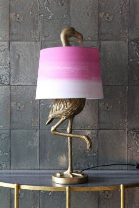 lifestyle image of antique gold flamingo table lamp with pink & white shade on gold table with grey tiled wallpaper background