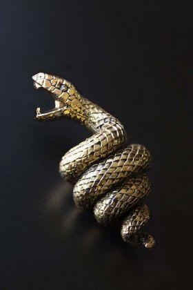 Lifestyle image of the Antique Gold Snake Bottle Opener on dark surface background